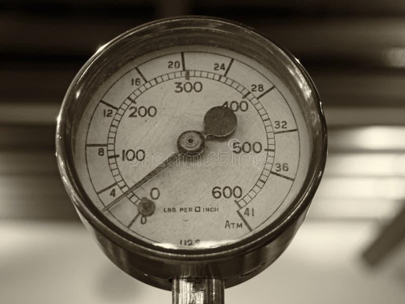 一个老发光的黄铜圆的压力表的乌贼属单色图象与在数字标记的一个圆的拨号盘的 免版税库存照片