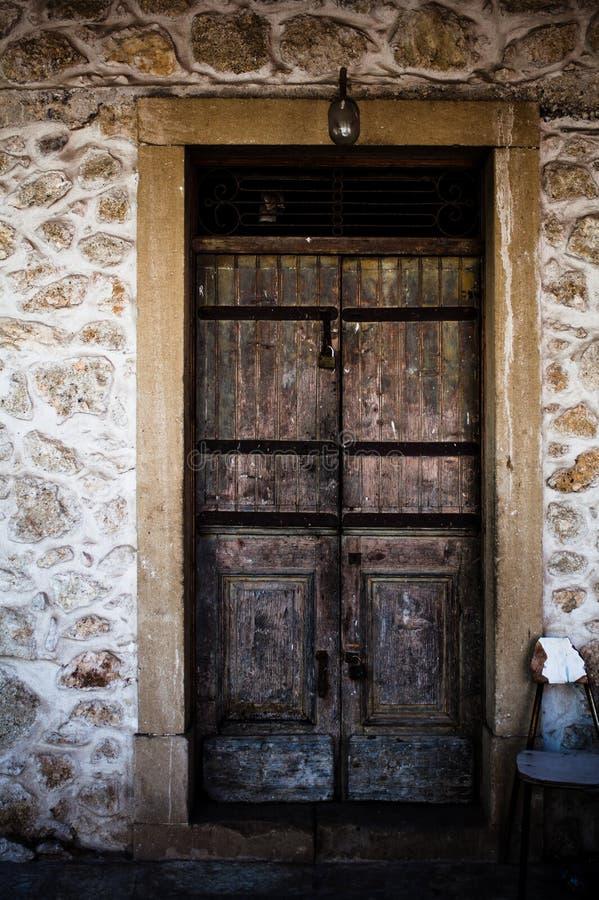 一个老古老木门在石头背景中在科孚岛希腊 在岩石的古色古香的城堡入口围住并且构筑做木头 义卖市场 图库摄影