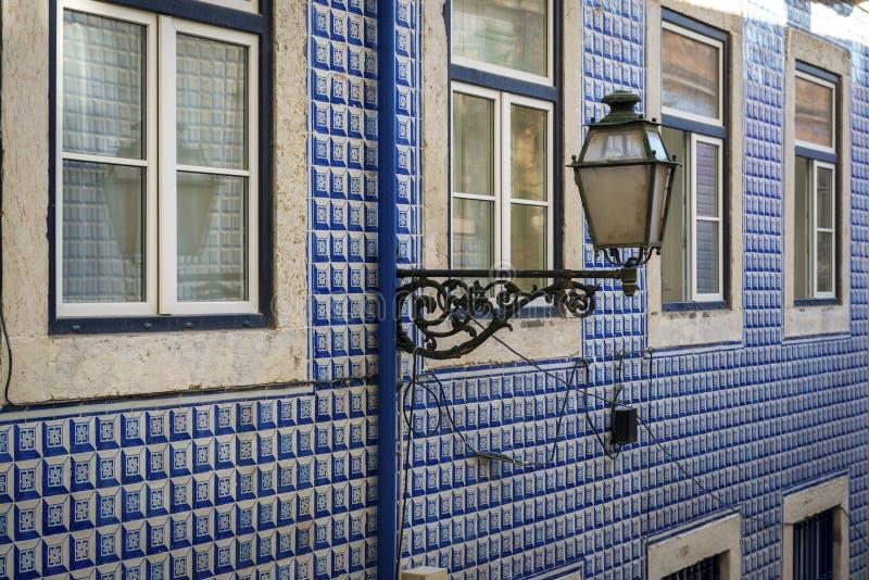 一个老大厦的门面的细节与葡萄牙语的在Alfama邻里铺磁砖Azulejo和一个灯岗位在里斯本 免版税库存图片