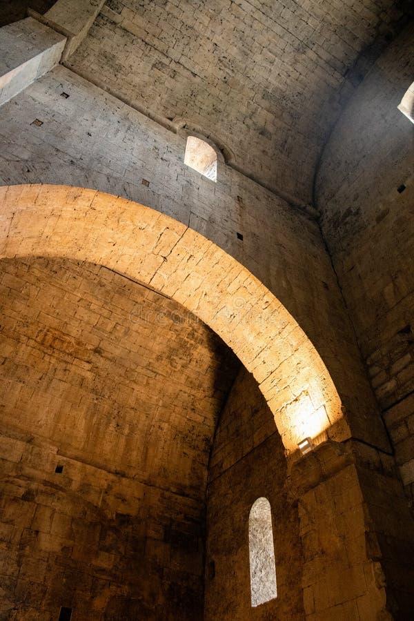 一个老大教堂/教会的内部在欧洲 曲拱、灯和窗口点燃的拱顶式顶棚和墙壁由后照由太阳 免版税库存图片
