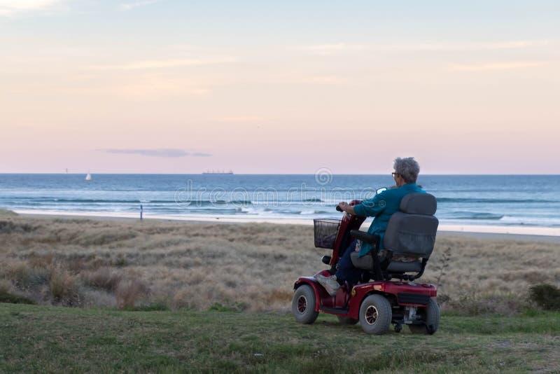 一个老妇人在海滩停放的一个电力的轮椅乘坐在日落时间,在偏僻的大气 老孤独的寡妇 库存照片