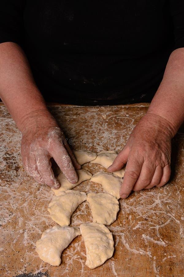 一个老妇人在黑暗的背景的一张桌连续做饺子 免版税库存照片