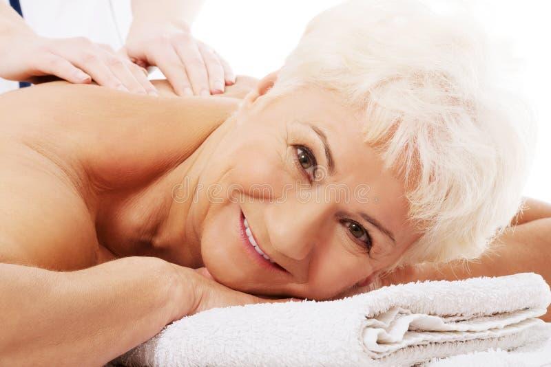 一个老妇人有按摩。温泉概念。 库存图片