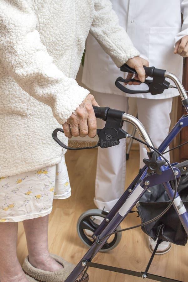 一个老妇人的手一个步行者的把柄的有闸的 护士帮助老妇人 库存照片