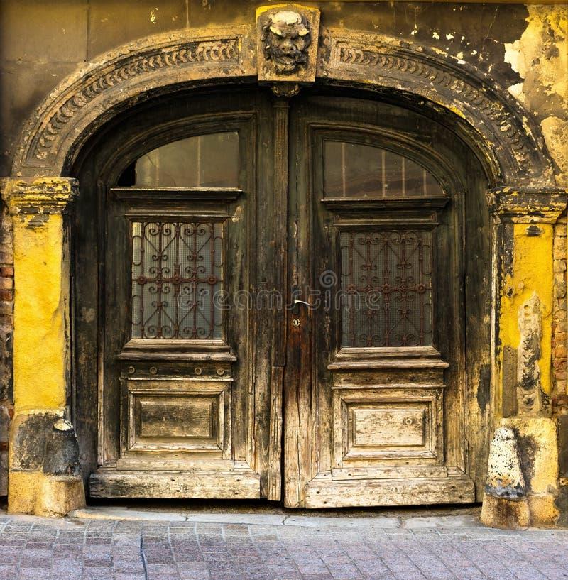 一个老巨型的被雕刻的木门和黄色门面,萨格勒布的看法与被雕刻的曲拱的在克罗地亚 免版税库存图片