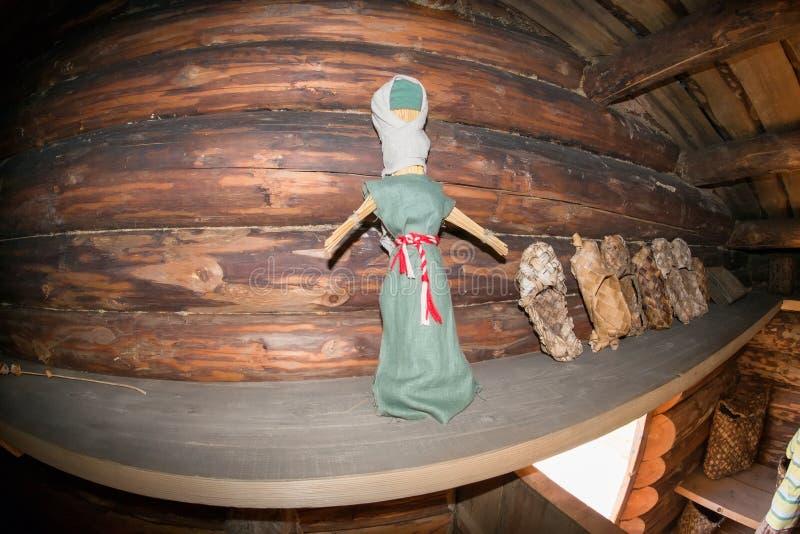 一个老布洋娃娃和韧皮鞋子在架子 库存照片