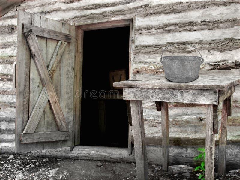 一个老日志棚子的前面 免版税库存照片