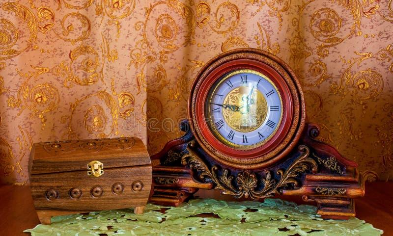 一个老时钟和小箱的照片在棕色背景 库存图片
