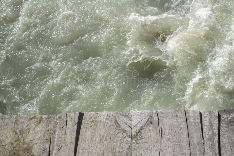 一个老木桥的边缘在一条坚固性山小河的 库存照片