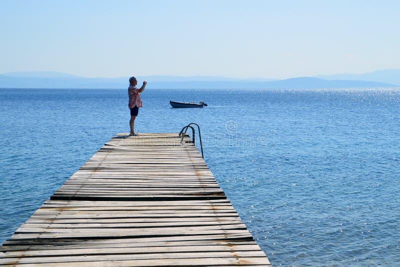 一个老木码头的人拍海的照片 免版税库存照片