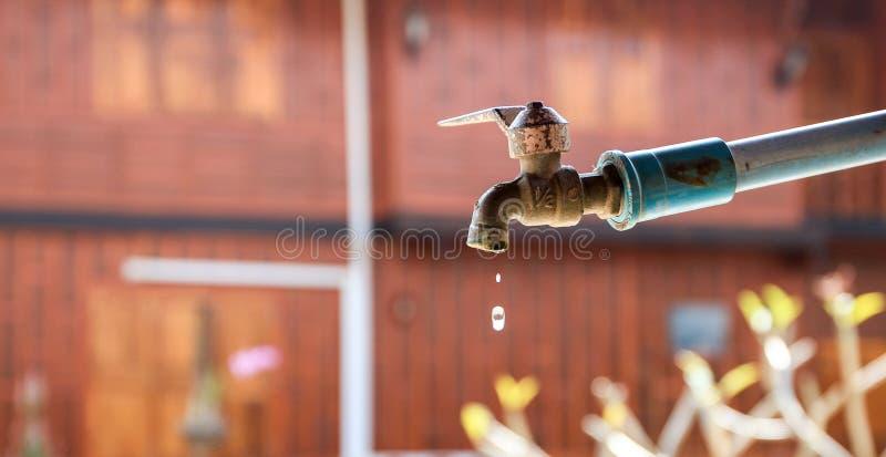 一个老水龙头在乡村droping的水中 免版税库存照片