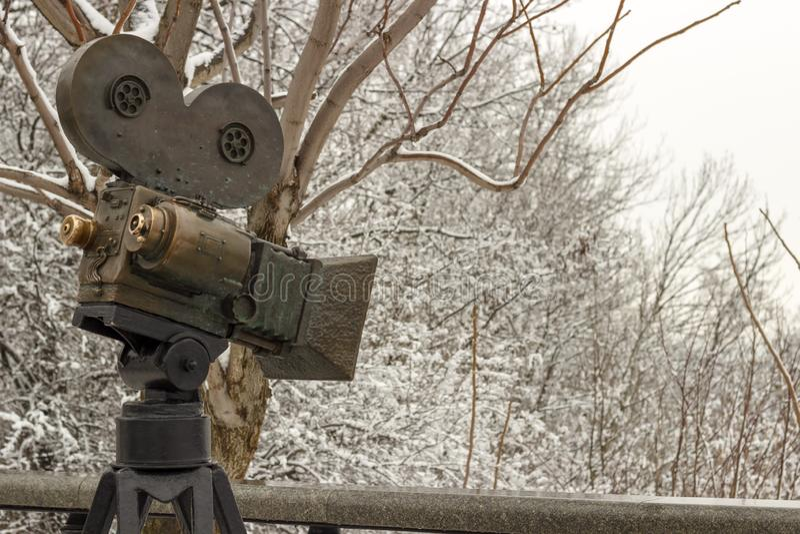 一个老电影摄影机,反对包括三脚架的天空背景,透镜,影片盘绕 免版税库存照片