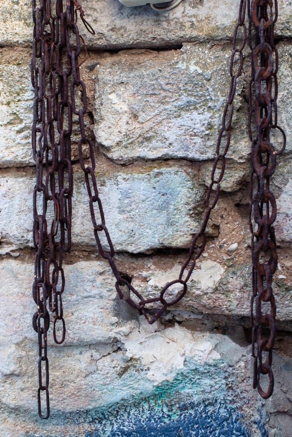一个老砖墙和一个生锈的链子对此背景的 库存图片