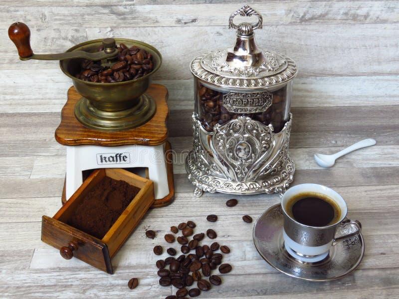一个老经典磨咖啡器、银色咖啡瓶子、一杯咖啡,瓷匙子、咖啡豆和剁碎的咖啡 减速火箭的样式 免版税库存照片