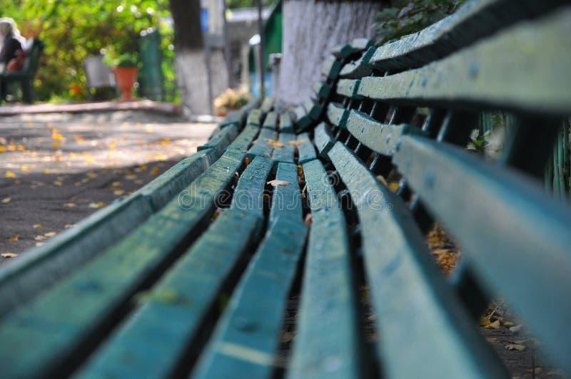 一个老绿色长木凳在秋天公园站立 图库摄影