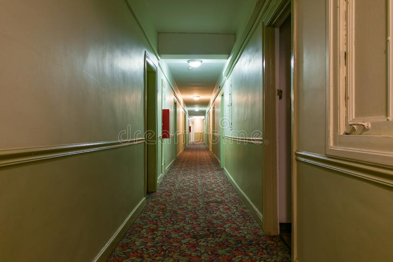 一个老美国公寓的长的黑暗和蠕动的走廊 免版税图库摄影
