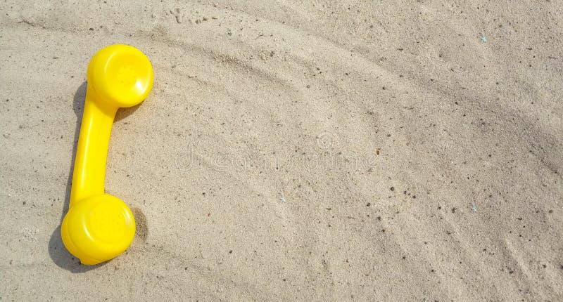 一个老葡萄酒电话的黄色电话在与拷贝空间的沙子说谎您的与联络的文本的 库存照片
