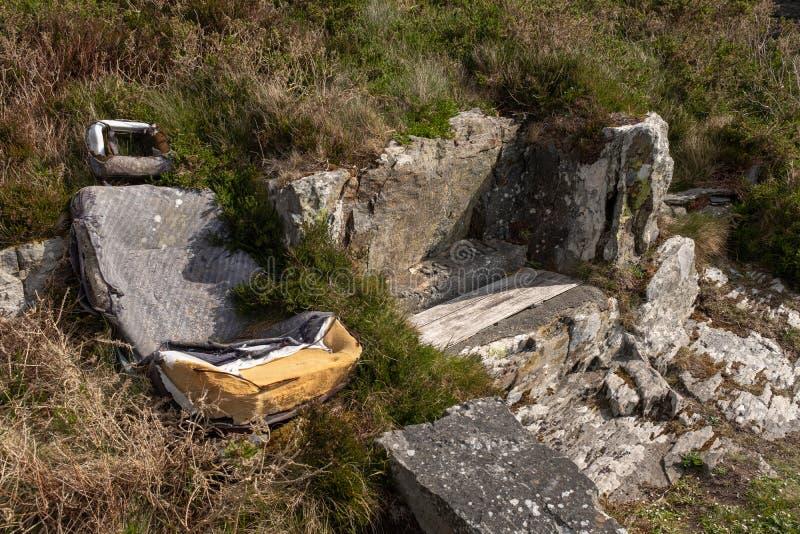 一个老被放弃的汽车座位在灌木和杂草围拢的山坡中间离开,可能作为住处用于孩子 免版税图库摄影