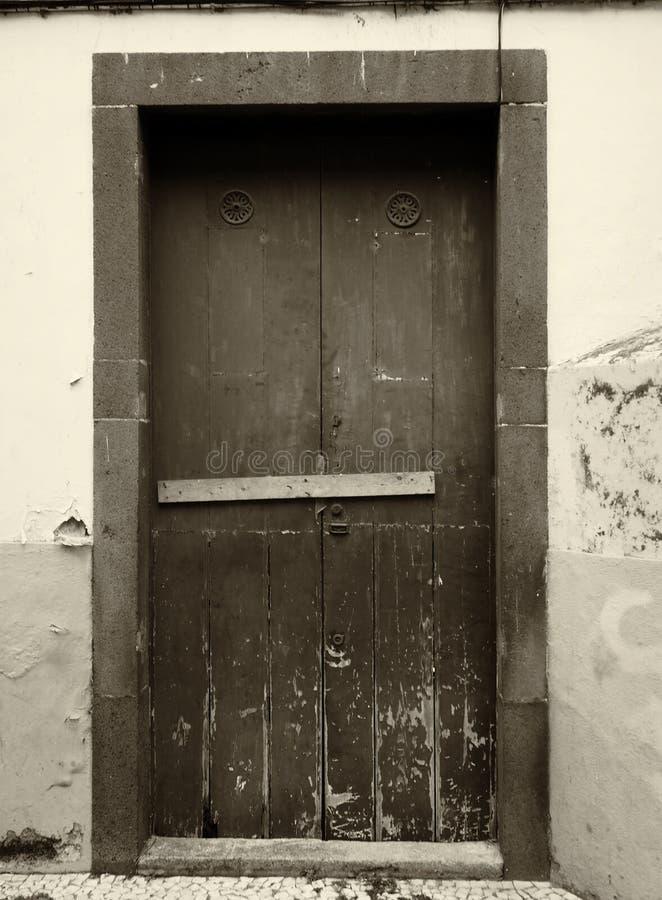 一个老被风化的木门的乌贼属单色图象被钉牢关闭与木酒吧和剥落的油漆在外部墙壁上 免版税图库摄影