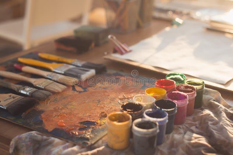 一个老调色板的角度图图片有油漆和树胶水彩画颜料集合的 清洗画家工作场所准备好画 免版税库存图片