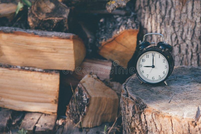 一个老闹钟设置了在十二和土气木表面和木柴上的一个星 库存图片