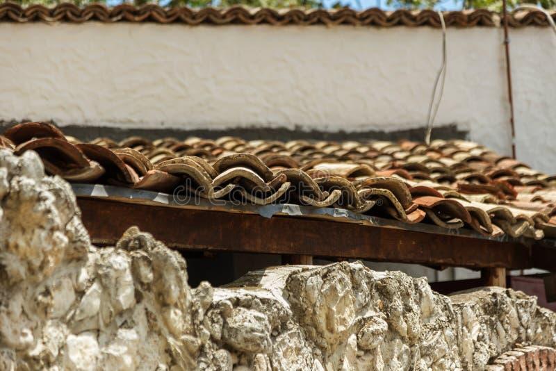 一个老陶瓷黏土瓦片的结尾视图的关闭在篱芭的黏土墙壁的 一个恶劣的被毁坏的村庄房子的老瓦  库存图片