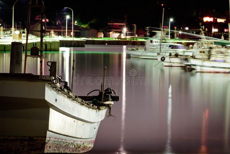 一个老,小和白色渔船在岸的晚上停放了 长的曝光射击和水是与反射的紫色颜色 免版税库存照片