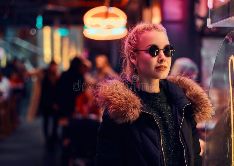一个肉欲的女孩身分在街道上的夜 有启发性牌,氖,光 免版税库存图片