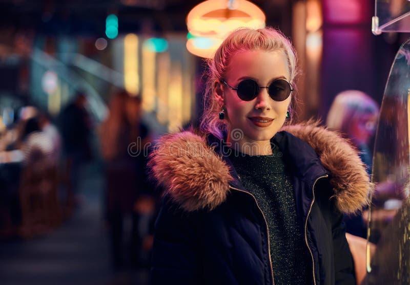 一个肉欲的女孩身分在街道上的夜 有启发性牌,氖,光 免版税库存照片