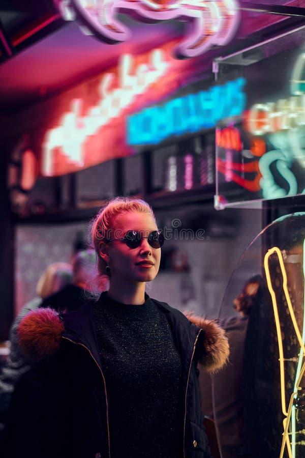一个肉欲的女孩身分在街道上的夜 有启发性牌,氖,光 库存图片