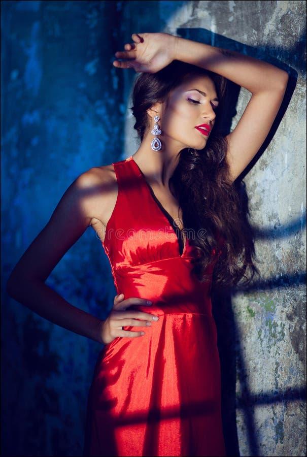 一个肉欲的性感的美丽的卷曲女孩的画象一件红色礼服的w 库存图片