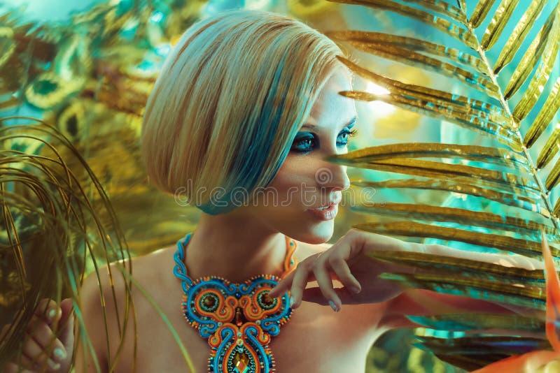一个肉欲的白肤金发的夫人的画象在热带 免版税库存照片