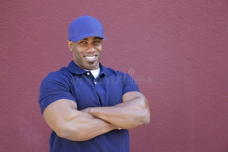 一个肌肉非裔美国人的送货人的画象有胳膊的横渡了在色的背景 库存照片