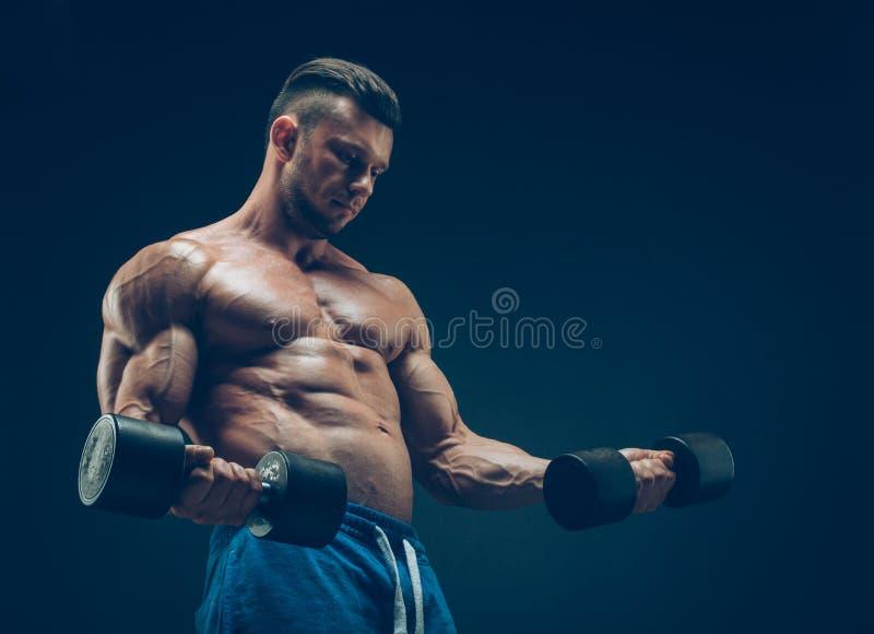 一个肌肉年轻人举的哑铃的特写镜头 图库摄影