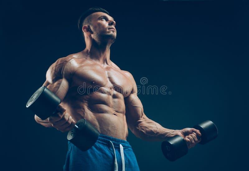 一个肌肉年轻人举的哑铃的特写镜头 库存图片