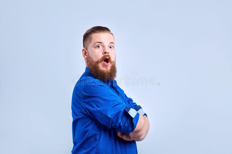 一个肥胖,有胡子的人看与他的嘴开放与一惊奇的前 免版税库存照片
