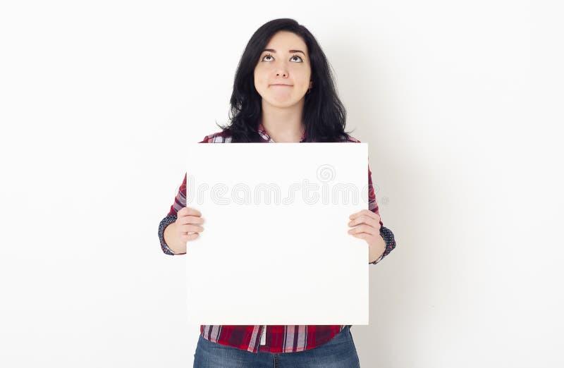 一个脸色憔悴的美女青年学生抬头,手里拿着一张白方形的空白 库存照片