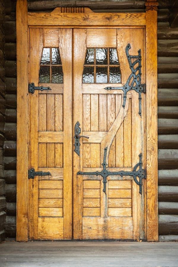 一个自然地木完成的门入口的室外正面图 与铁铰链配件的土气传统装饰样式 免版税库存照片