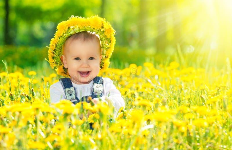一个花圈的愉快的女婴在有黄色花的草甸在t 免版税图库摄影