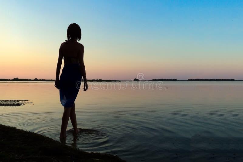 一个苗条女孩的剪影湖背景的 免版税库存图片