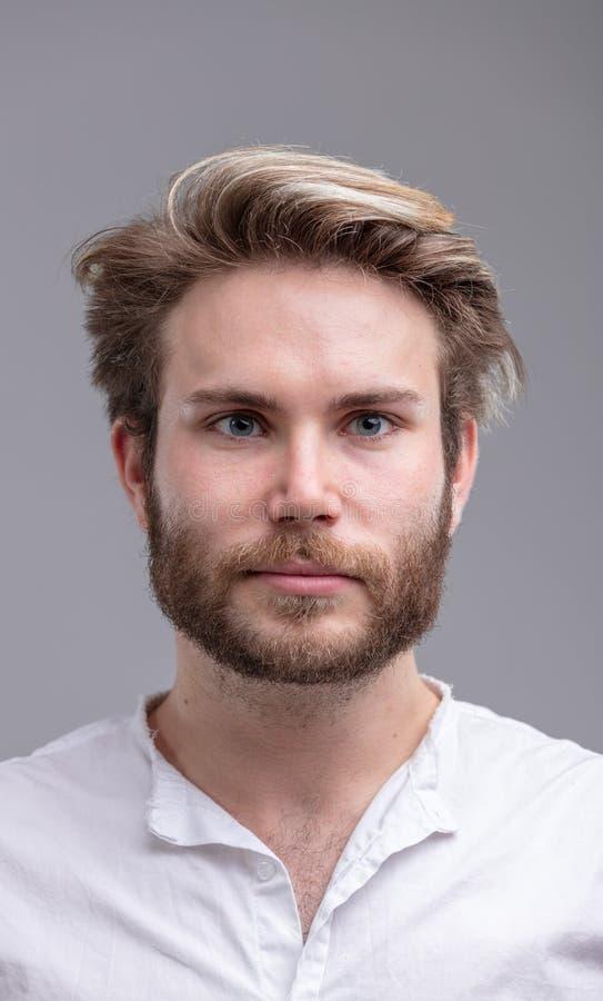 一个英俊年轻有胡子人认为的画象 库存照片