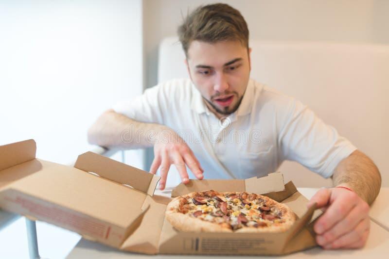 一个英俊的人凝视与饥饿的神色的薄饼 人采取比萨饼 免版税图库摄影