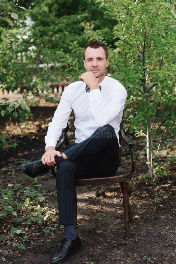 一个英俊的人和在自然的蝶形领结的画象一件白色衬衣的 库存图片