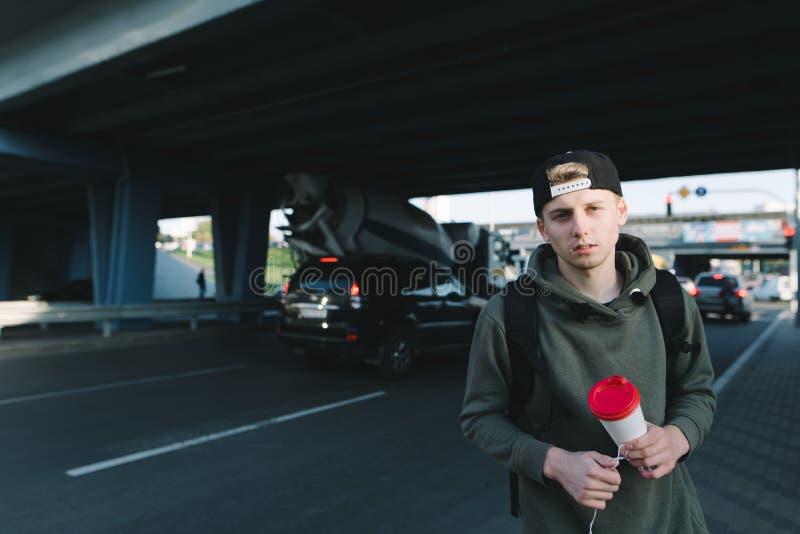一个英俊的人用咖啡递身分反对路和汽车的后面在桥梁下和看照相机 免版税库存图片