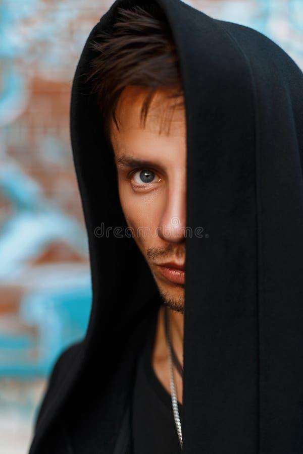 一个英俊的人的画象一个黑敞篷的 隐藏的表面 免版税库存照片