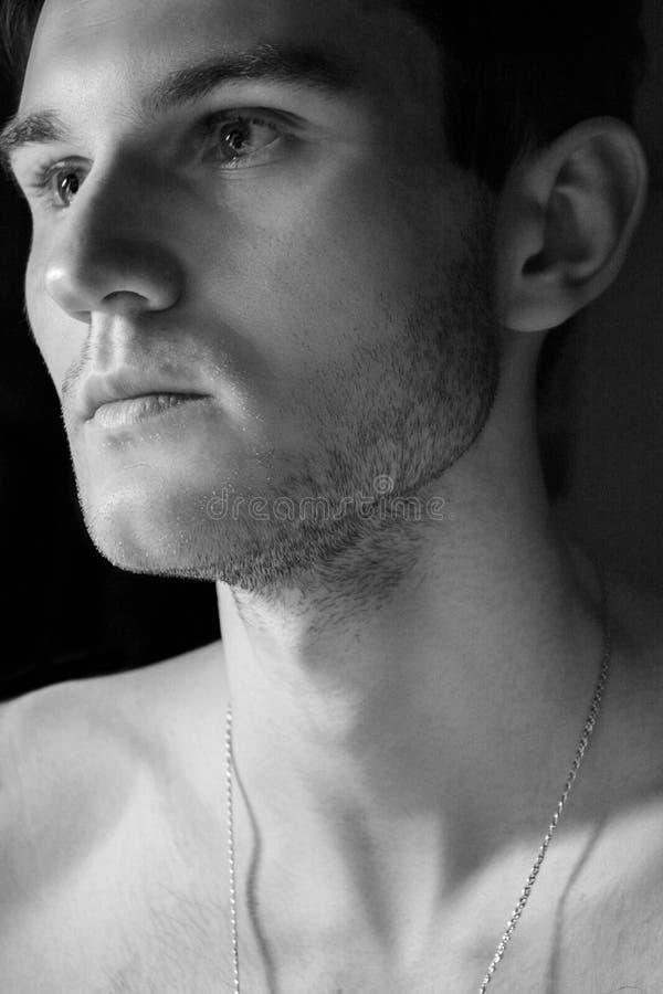 一个英俊的人的画象有赤裸躯干的 一个从灯的特写镜头在一个暗室和光的照片 柔光 绿眼的增殖比 图库摄影