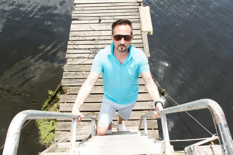 一个英俊的商人在度假与游艇的在船坞和木码头背景 laddering的太阳镜的人  图库摄影