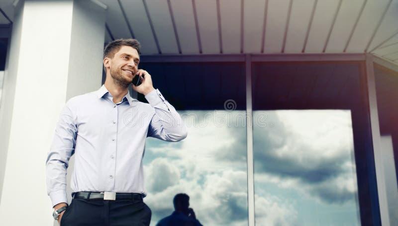 一个英俊的商人的画象在办公楼backgroun的 免版税图库摄影