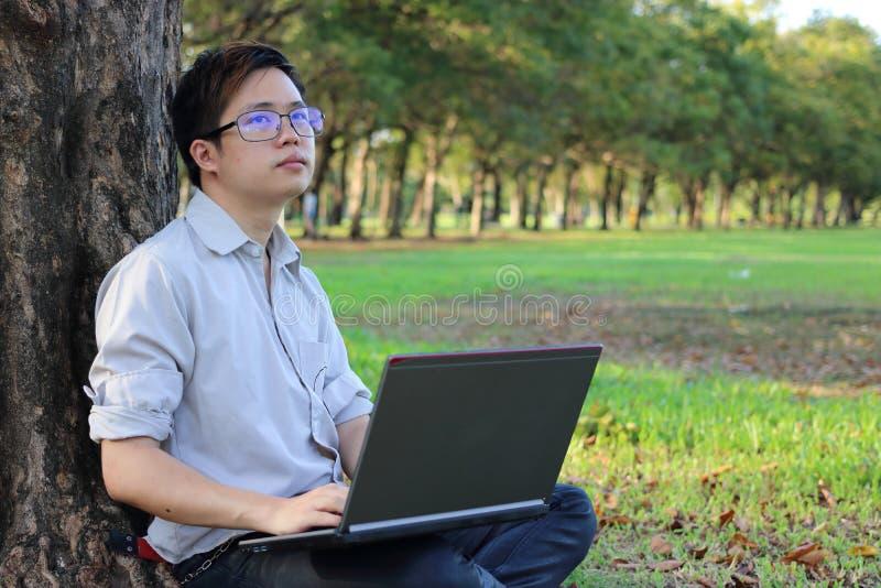 一个英俊的年轻人的画象有倾斜在树和看很远在与拷贝spac的自然背景的便携式计算机的 库存图片