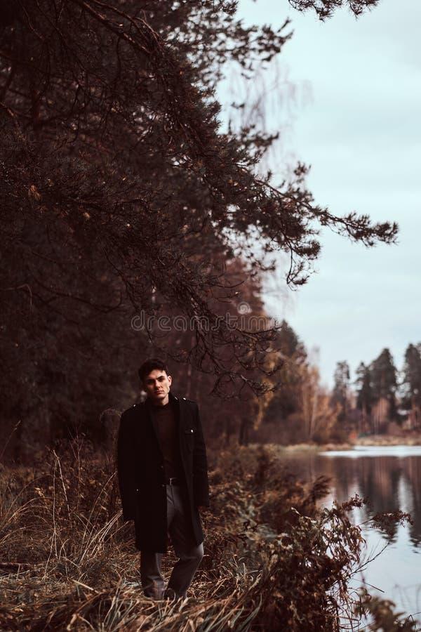 一个英俊的年轻人身分在秋天森林里 库存照片